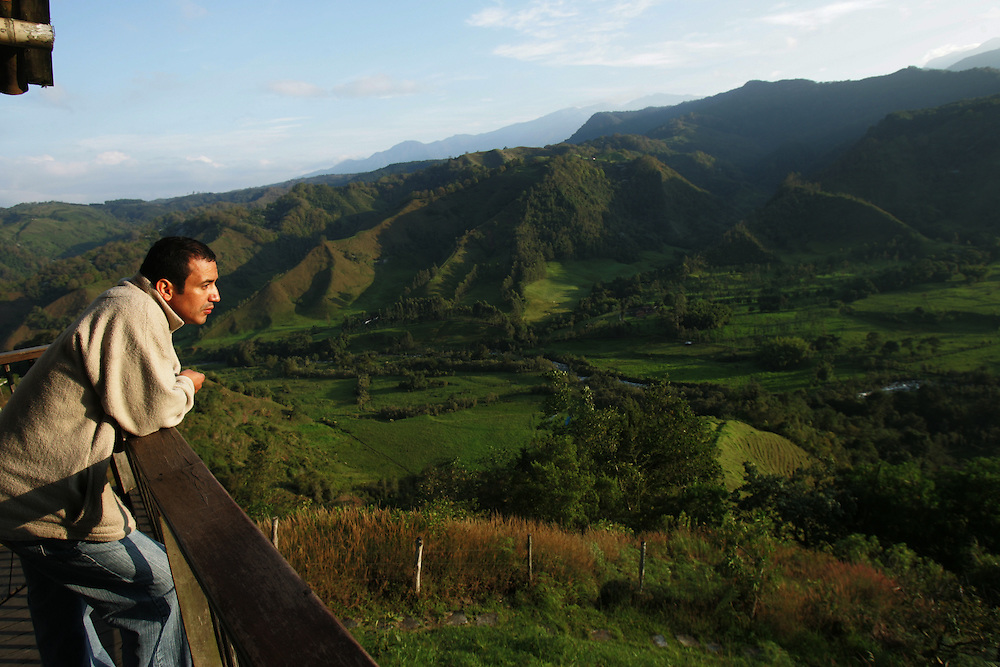 A man takes in the early morning view looking in to the Coccora valley in the heart of Colombian coffee country. The tourism industry is slowly emerging in Quindio, the Colombian coffee country.  Old coffee haciendas have been turned into new hotels catering to tourists.  The countryside, some of the most beautiful in the country, is a popular weekend getaway spot where visitors can participate in a variety of outdoor activities as well as learn about coffee production.