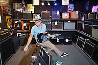Young male customer plugging electric guitar to speaker