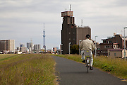 An old man rides a bicycle alonside the Arakawa River near Kita Senju in Tokyo, Japan Friday October 12th 2012