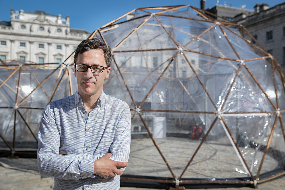 © Licensed to London News Pictures. 18/04/2018. London, UK. British artist Michael Pinsky stands in front of his Pollution Pods, a new sensory work, installed in the courtyard at Somerset House in London to mark Earth Day 2018. A series of five connecting domes recreate the pollution from London, Beijing, São Paulo, New Delhi and Tautra in Norway. Visitors are invited to experience first-hand the difference in the air quality of global environments. The Pollution Pods are open until 25th April 2018, including Earth Day on the 22nd April. Photo credit: Peter Macdiarmid/LNP
