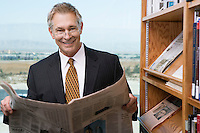 Businessman reading newspaper library, portrait