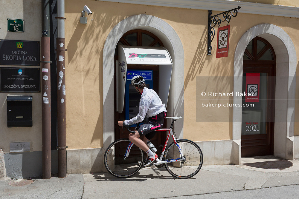 A cyclist takes cash from an ATM at a branch of Gorenjska Banka in the central Slovenian rural town of Skofja Loka, on 25th June 2018, in Skofja Loka, Slovenia.