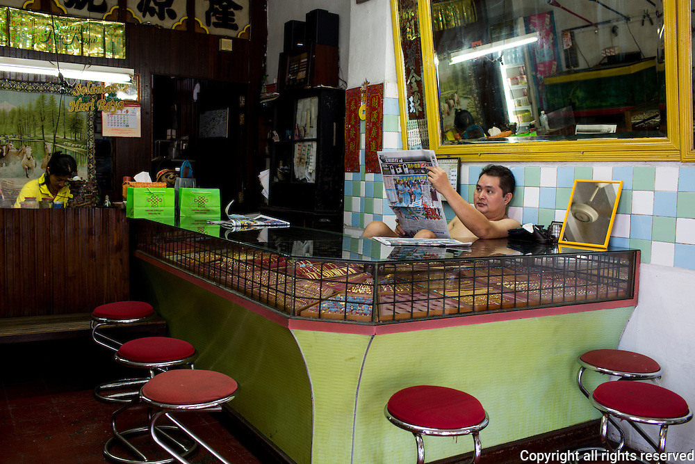 A man reads the newspaper in a gold shop in Balik Pulau, Penang, Malaysia