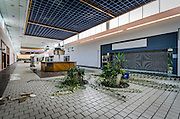 """Abandoned Miracle City Mall<br /> <br /> The advent of the human space program in 1961 transformed Titusville in just 10 years from a sandy and soporific town of about 6,000 into a vigorous city of 31,000. The rapid growth inspired the """"Miracle City"""" sobriquet adopted by the mall's planners.<br /> <br /> Miracle City Mall opened in 1968, built on 32 acres and covering 275,000 square feet of floor space.<br /> <br /> JCPenney and Belk Lindsey(later Belk's) anchored the mall, with the spaces between them occupied by the likes of Thom McAn (a shoe store), McCrory (a department store), Vogue and Lerner women's fashions, a Hallmark card shop, Zales Jewelry and a Walgreens with a snack bar. Within a few years, the mall added an outlying building just north of it, containing a twin movie theater and a grocery store.<br /> <br /> Bob Socks, a former city councilman and an original tenant, operated an Orange Julius stand in the mall for three years before taking a job as manager of the Walgreens at the other end of the mall. Alden Curfman, newly relocated with his family from North Dakota, was running a Karmelkorn shop in the mall. In 1971, he began leasing the Orange Julius kiosk from Socks and eventually bought the franchise.<br /> <br /> Curfman's son, Dave, managed the Orange Julius stand and later took over the business. When the deal with Orange Julius expired, the stand became known as """"Dave's"""" hot dog stand. There are speculations as to what caused the mall's decline, but many agree that Miracle City was hit hard when the Walmart Supercenter opened in 1995. By the mid-2000s, the mall was just a shadow of it's former self. Belk's had left, leaving JCPenney's as the lone anchor and only a handful of stores remained, including's """"Dave's"""" remained. Due to the economic depression, the site showed signs of deterioration as there was barely any maintenance done.<br /> <br /> The end of the space program in 2011 was a huge blow to the economy of Titusville… and a killing blo"""