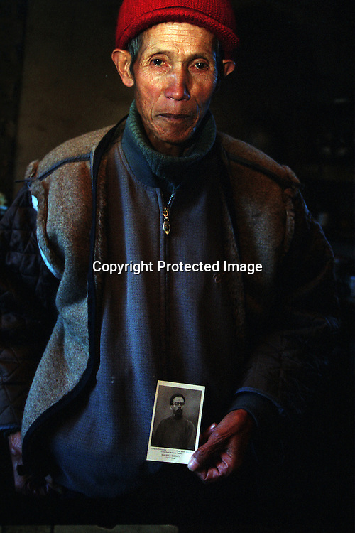 "CIZHONG, DECEMBER 17, 2000: Bernard, 75, holds a picture of Maurice Tournay,one of the French missionaries who built the Catholic church in Cizhong at then end of the 19th century, Yunnan province , December 17, 2000. Bernard went to jail for 22 years after the foreign missionaries left Cizhong in 1952 for having assisted them . he passed away in 2003..The church in Cizhing is believed to be the real life model for James Hilton's famous novel "" lost Horizon""- a description of Shangri-La-..Maurice Tournay is one of the catholic martyrs who were canonized by pope John Paul II on October 1, 2000.. . ."