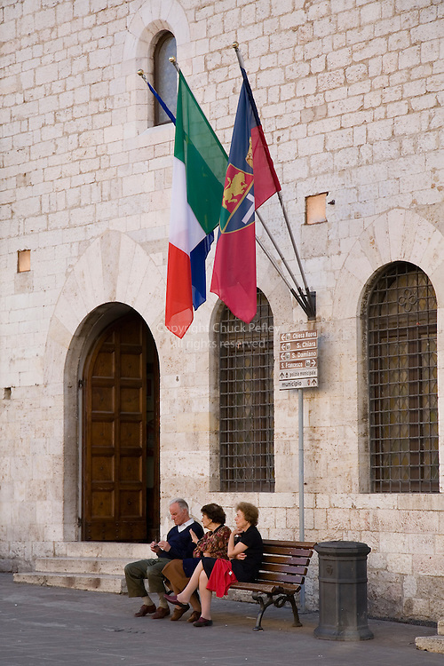 Three people sit on bench on the Piazza Del Comune in front of the Palazzo Comunale in the Umbrian hilltown of Assisi, Italy PG<br />