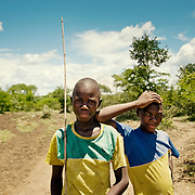 Young african boys on scenic village road with clouds