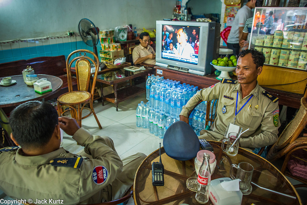 """04 FEBRUARY 2013 - PHNOM PENH, CAMBODIA:  Cambodian police officers sit in a coffee shop in Phnom Penh during the cremation of King-Father Norodom Sihanouk. Norodom Sihanouk (31 October 1922- 15 October 2012) was the King of Cambodia from 1941 to 1955 and again from 1993 to 2004. He was the effective ruler of Cambodia from 1953 to 1970. After his second abdication in 2004, he was given the honorific of """"The King-Father of Cambodia."""" Sihanouk died in Beijing, China, where he was receiving medical care, on Oct. 15, 2012.   PHOTO BY JACK KURTZ"""