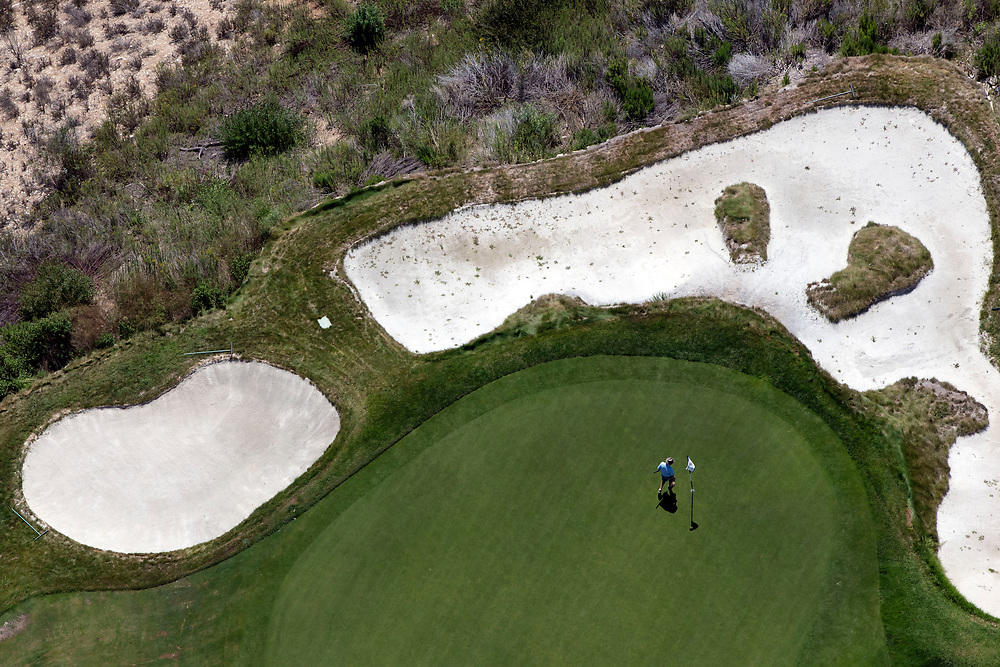 A man golfs at the Trump National Golf Club, Los Angeles  in this aerial photograph taken during the historic drought over Rancho Palos Verdes, California, U.S., on Monday, August 31, 2015. Owned by The Trump Organization, the course was formerly known as Ocean Trails Golf Club, an 18-hole course designed by Pete Dye, which was about to open when a landslide occurred. Donald Trump bought the property known for it's views of the Pacific Ocean in 2002. © 2015 Patrick T. Fallon