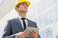 Young male architect holding tablet PC against building