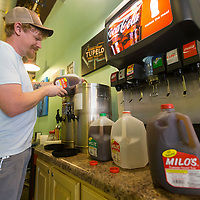Jason Hayden, co-owner of Cafe 212, pours gallons of sweet tea into their sweet tea dispenser Friday morning at the restaurant. Hayden said they usually brew their sweet tea in house, but had to go pick up gallons to serve to customers with the boil water notice that is in effect.