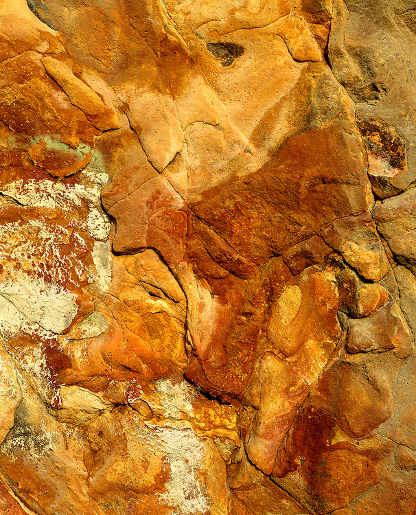 Orange and cinnamon colored rocks at Harris Beach State Park form a collage of shapes and textures, Oregon. ©Ric Ergenbright