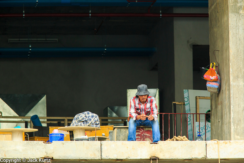 16 OCTOBER 2012 - BANGKOK, THAILAND: A worker takes a break at a residential condominium project on Th Phaya Thai near the intersection with Phetchaburi Rd. in Bangkok. The global economic slowdown had little visible effect in Bangkok. Construction projects dot the city of 12 million and development continues unabated.    PHOTO BY JACK KURTZ