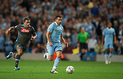 MANCHESTER, ENGLAND - Wednesday, September 14, 2011: Manchester City's Carlos Tevez in action against SSC Napoli's Walter Gargano during the UEFA Champions League Group A match at the City of Manchester Stadium. (Photo by Chris Brunskill/Propaganda)