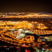 And aerial shot taken from a helicopter at about 500 feet of Newark Liberty International Airport (EWR) at night, with the city lights showing brightly. Please note that there is some high ISO noise at full resolution.