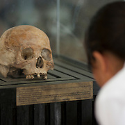 A human skull is viewed by a Cambodian High School student  at the Toul Sleng Genocide Museum in Phnom Penh, Cambodia, March 13, 2005.  According to government sources about 500 people a day visit the museum where an estimated 14,000 people were tortured and later executed.  The building was a high school in Phnom Penh before being used as a prison by the Khmer Rouge in 1975.