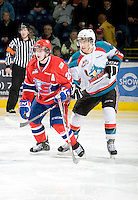 KELOWNA, CANADA, JANUARY 4: Steve Khun #20 of the Spokane Chiefs is checked by Colton Heffley #25 of the Kelowna Rockets as the Spokane Chiefs visit the Kelowna Rockets on January 4, 2012 at Prospera Place in Kelowna, British Columbia, Canada (Photo by Marissa Baecker/Getty Images) *** Local Caption ***