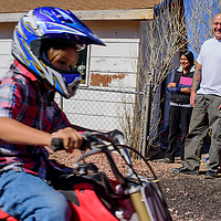 Quinn Kelley, right, and Malaina Kelley watch as their son Peter Kelley races past on his dirtbike in the field behind their home in Gallup Wednesday.