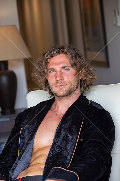 sexy man with long brown hair in a smoking jacket at home