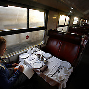 "A passenger waits for breakfast in the dining car of the Nairobi-Mombasa train as the sun comes up. The approximately 300 mile journey took 16 hours this trip. Also known as the ""Lunatic Express"", It was the railway line that built Kenya, linking the port town of Mombasa.through the capital, Nairobi, to the shores of Lake Victoria and on to the.Ugandan capital, Kampala. It cost $5m (in 1894 money) and countless workers died during its construction. There were derailments, collisions, tribal raids and attacks by lions. Yet despite becoming one of Kenya's national treasures and a vital economic artery for east Africa, the railway now lies in a state of disrepair. A South African consortium has taken it over and plans to invest millions, returning it to its former glory. But there has been a row over the railway's financing which may yet derail the .project. .."