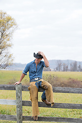 All American cowboy sitting on a  wooden fence