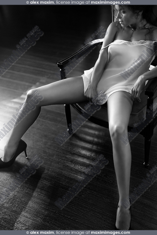 Artistic sensual black and white photo of a beautiful young woman sitting in a bold seductive pose in a chair with her long sexy legs in high heel shoes spread wide apart