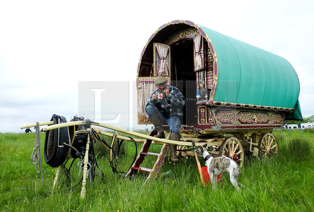 © Licensed to London News Pictures. <br /> 05/06/2014. <br /> <br /> Appleby, Cumbria, England<br /> <br /> Trevor Jones from the Wirral has a cup of tea as he sits on the steps of his Bow top wagon as gypsies and travellers gather during the annual horse fair on 5 June, 2014 in Appleby, Cumbria. The event remains one of the largest and oldest events in Europe and gives the opportunity for travelling communities to meet friends, celebrate their music, folklore and to buy and sell horses.<br /> <br /> The event has existed under the protection of a charter granted by King James II in 1685 and it remains the most important event in the gypsy and traveller calendar.<br /> <br /> Photo credit : Ian Forsyth/LNP