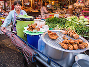 13 FEBRUARY 2014 - BANGKOK, THAILAND:  A fried chicken vendor pushes his cart through Khlong Toei Market, the largest wet market in Bangkok.    PHOTO BY JACK KURTZ