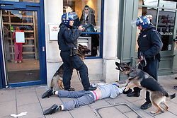 © Licensed to London News Pictures . FILE PICTURE DATED 07/08/2011. Enfield , UK . Riot police with dogs detain a man outside HSBC in Enfield Town Centre as others break in and take cover in the outer foyer of the bank . Hundreds gathered and broke in to shops following messages sent via Blackberry Messenger . Following a night of riots and looting in Tottenham , looting spreads to other parts of London . Photo credit : Joel Goodman/LNP