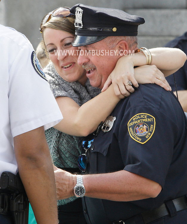 Middletown police officer Michael Canonico gets a hug from his daughter Amy Canonico after walking through a line of fellow officers in a ceremony marking the final day of his 32 years on the department. Amy Canonico surprised her father by coming up from Orlando, Fla., for the event.