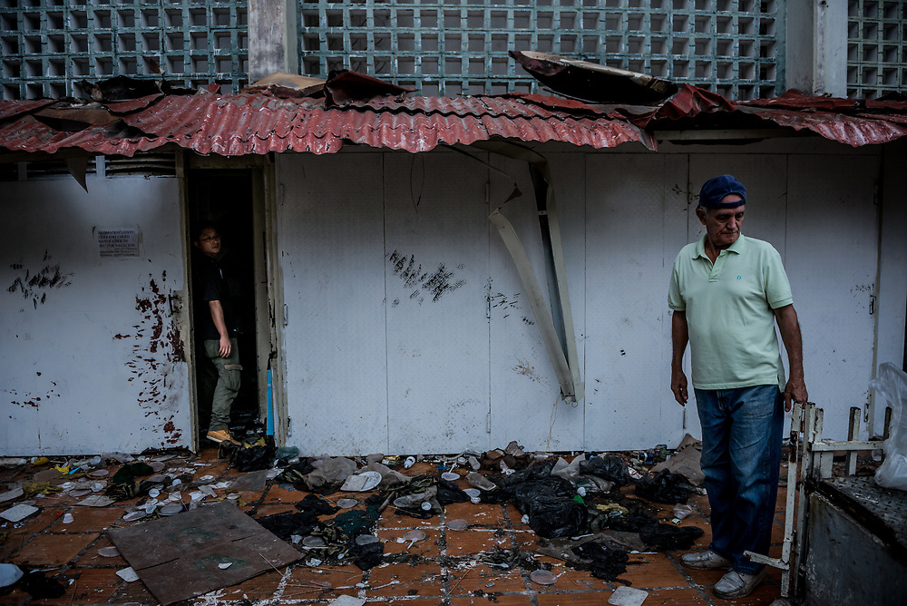 CARACAS, VENEZUELA - APRIL 21, 2017:  Men inspect the damage to Vicruz supermarket, that was one of over a dozen stores looted late last night in El Valle, a working class neighborhood in Caracas. The streets of Caracas erupted into a night of riots, looting and clashes with National Guardsmen as anger from two days of pro-democracy protests spilled into unrest in working class neighborhoods and slums. Shots rang out throughout the night in El Valle, a neighborhood of mixed loyalties, as armored vehicles struggled to contain crowds of looters. At one point during the night, clashes became so heavy that a nearby children's hospital was evacuated after the ward filled with tear gas. The government said they were responding to an attack on the hospital by opposition protestors.  PHOTO: Meridith Kohut