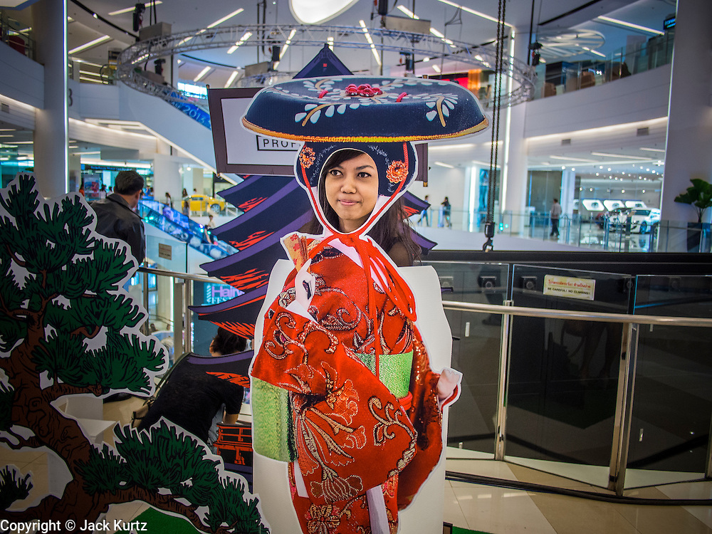 24 JULY 2013 - BANGKOK, THAILAND: A woman stands in a photo cut out of Japanese woman of the 19th century at the Hairworld Festival in Siam Paragon, an upscale shopping mall in Bangkok, Thailand.        PHOTO BY JACK KURTZ