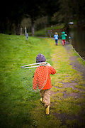 A boy with a fishing net walking in rain boots near Portland, Oregon
