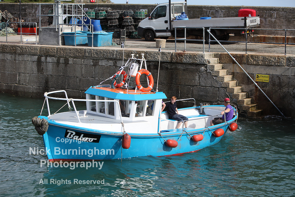 "Newquay Harbour, Newquay, Cornwall, August 6, 2015.  High tide and a sunny morning brings a range of tourist activities to Newquay Harbour. The ""Baloo"" heads out on a pleasure trip from the harbour."