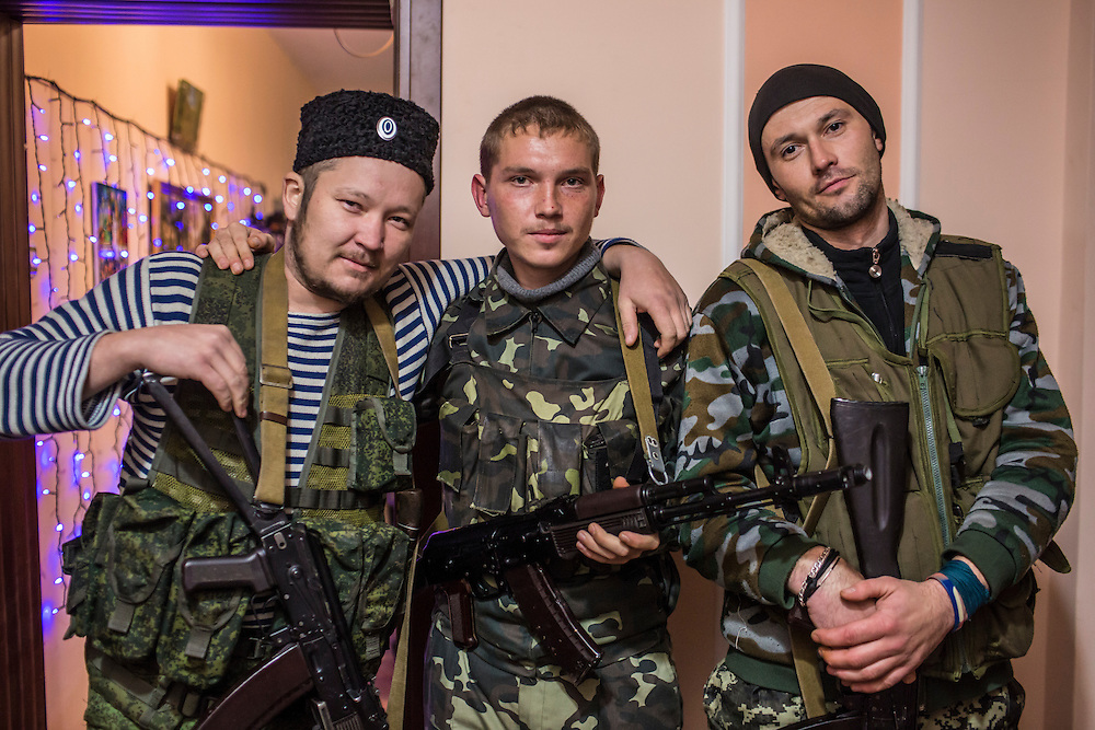 PERVOMAISK, UKRAINE - NOVEMBER 20, 2014: Ruslan Alyfyrenko, Petr Khokhlov, and Zhenya Gritzan,  members of the First Cossack Regiment Named Platov of the Great Don Army, pose for a portrait at the dormitory where they are stationed in Pervomaisk, Ukraine. CREDIT: Brendan Hoffman for The New York Times