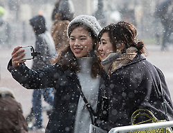 © Licensed to London News Pictures. 26/02/2018. London, UK. Tourists take a selfie during a snow shower at Buckingham Palace as a cold front sweeps in from the east - with heavy snow expected later in parts of the UK. Photo credit: Peter Macdiarmid/LNP