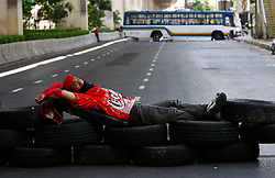 An anti-government protester lies on tires stacked up as a blockade as they prepare to face-off the Thai army during pitched battles on the streets of Bangkok, Thailand, 13 April 2009. Thai Prime Minister Abhisit Vejjajiva declared a state of emergency in Bangkok to quell anti-government protests that forced the cancellation of the ASEAN summit in Pattaya. Thai soldiers fired shots at protestors driving buses at them and used tear gas against demonstrators blocking a main road junction in Bangkok in a major escalation of political violence in the kingdom
