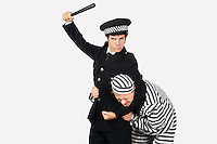 Portrait of police officer with nightstick arresting male prisoner against gray background