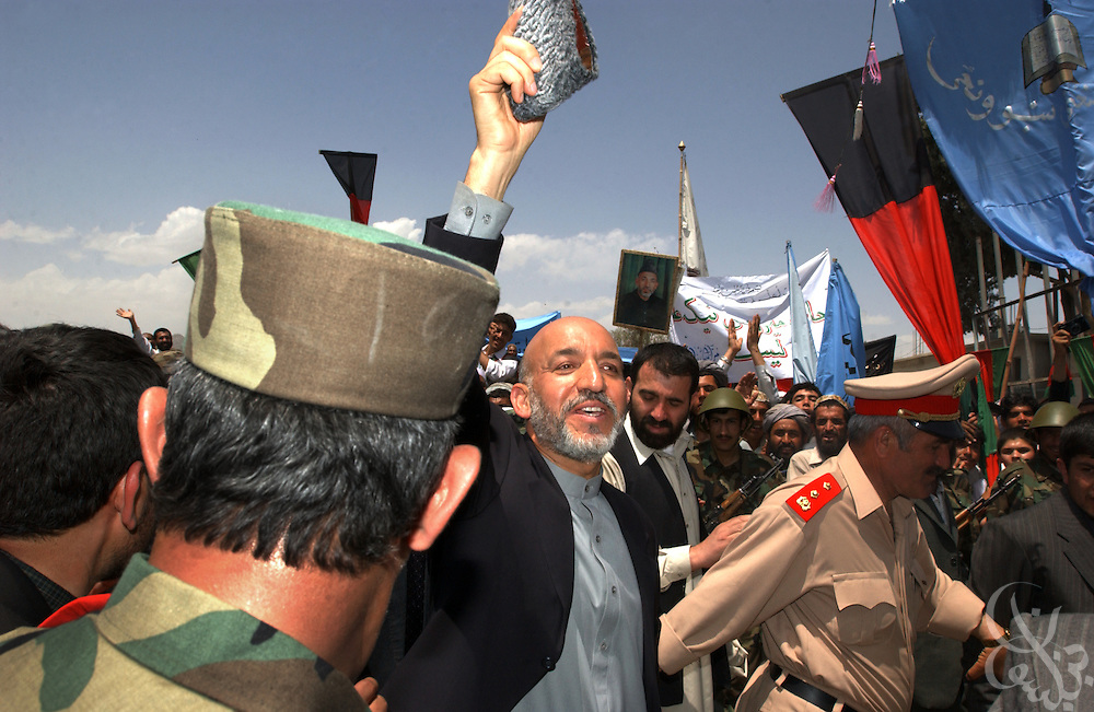 Interim Afghan leader Hamid Karzai waves to supporters behind a security cordon May 04, 2002 after arriving in the southern Afghan city of Kandahar. The visit by Karzai to the city, his first since assuming power, is significant because of the city's history as a former Taliban stronghold.