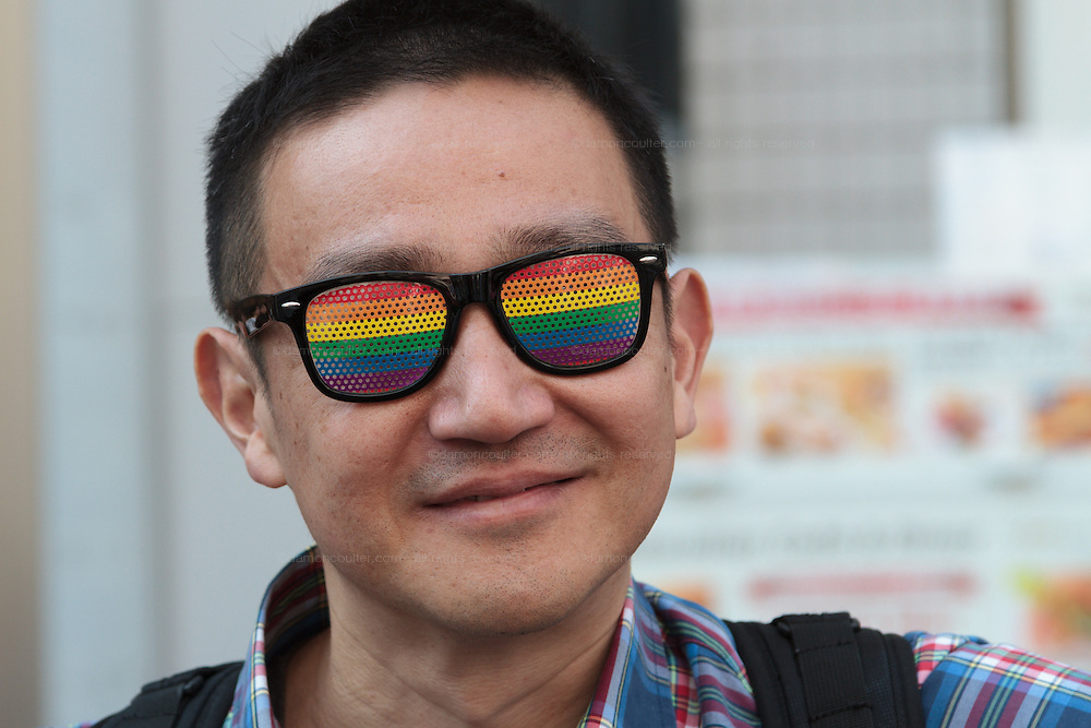 A Japanese man wears rainbow coloured glasses at The Rainbow Pride Event in Yoyogi Park, Shibuya, Tokyo, Japan. Sunday, April 26th 2015. This is the forth annual celebration of LGBT issues in Tokyo and forms part of a wider Rainbow Week. About 5% of the Japanese population identify as homosexual and this event hopes to foster a society where they can live equally and without prejudice.