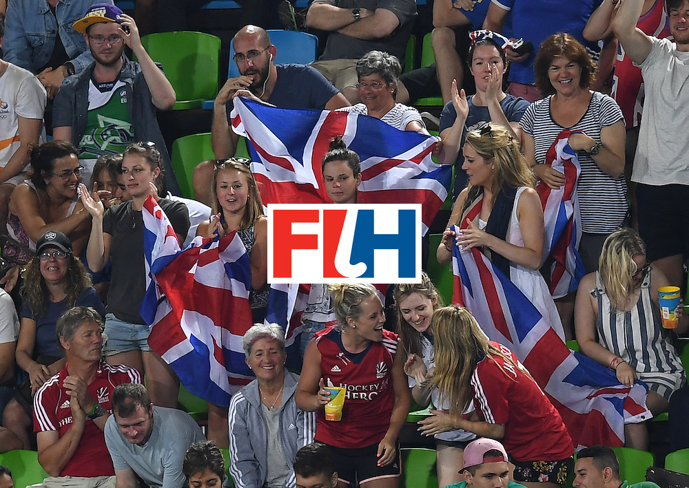Britain fans hold up flags during the men's field hockey Brazil vs Britain match of the Rio 2016 Olympics Games at the Olympic Hockey Centre in Rio de Janeiro on August, 9 2016. / AFP / MANAN VATSYAYANA        (Photo credit should read MANAN VATSYAYANA/AFP/Getty Images)