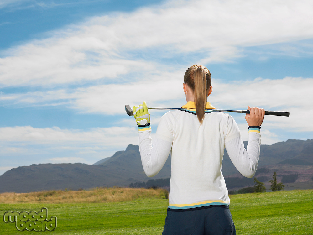Young woman on golf course back view