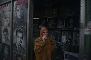 Cairo, Egypt Dec. 4, 2012-Surrounded by portraits of Egypt's political and cultural heroes, a woman watches a crowd of opposition protesters march by her portrait studio on the way to the presidential palace in the Heliopolis neighborhood of Cairo. Protests over a decree President Mohamed Morsi issued Nov. 22 giving himself near-absolute power have entered a 12th day, with Tuesday being the first day that crowds have marched to the palace. (Photo by Miguel Juarez Lugo)