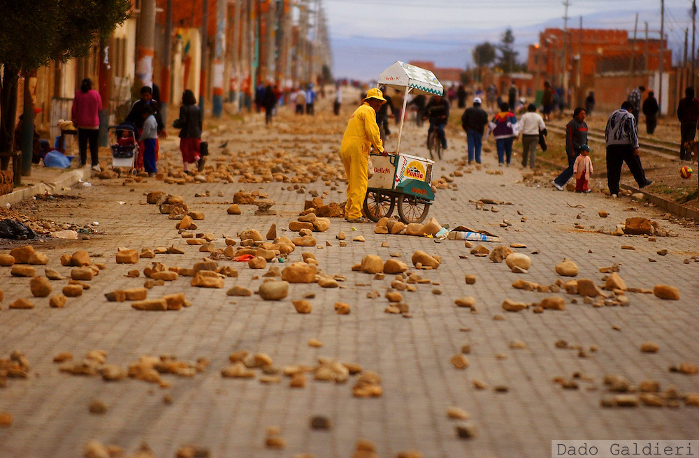 A Bolivian street vendor makes his way amid thousands of stones blocking a road in El Alto , Bolivia on Sunday, October 12, 2003. Thousands of inhabitants of impoverished city of El Alto clashed with Bolivan army forces that were escorting a convoy with 12 gas truck to supply La Paz with fuel(Dado Galdieri)