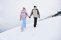 Couple walking up snow-covered hill back view low angle view