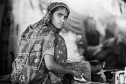 A black and white portrait of a young girl with a serious look cooking in a tent at the Pushkar camel fair, Pushkar, Rajasthan, India