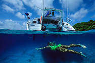 Enjoying the pleasures of barefoot sailing charter in clean clear Tongan waters. South Pacific.