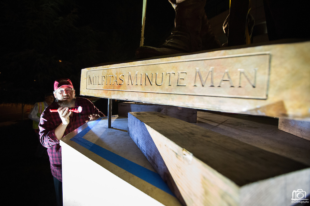 Wyoming sculptor David Alan Clark guides the 12-foot Milpitas Minute Man sculpture into place outside Milpitas City Hall in Milpitas, California, on January 24, 2014.  The sculpture took 10 months to complete, and weighs approximately 2,500 pounds. (Stan Olszewski/SOSKIphoto)
