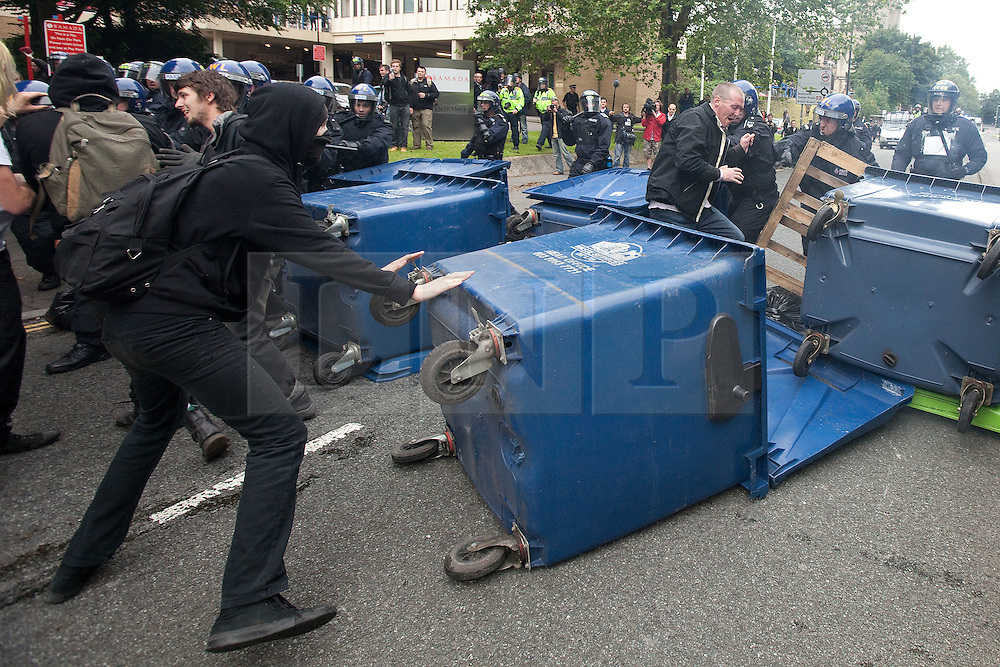 © Licensed to London News Pictures. 14/07/2012. Bristol , UK . Anti fascist protesters clash with police as they attempt to block the route for EDL supporters to leave their demontration . The protesters roll wheelie bins at police and set them alight . The English Defence League hold a march and demonstration in Bristol . Photo credit : Joel Goodman/LNP