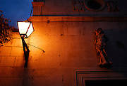 Detail of lamp and wall at night, Church of Saint Sebastian (Crvca Sveti Sebastijan). Trogir, Croatia